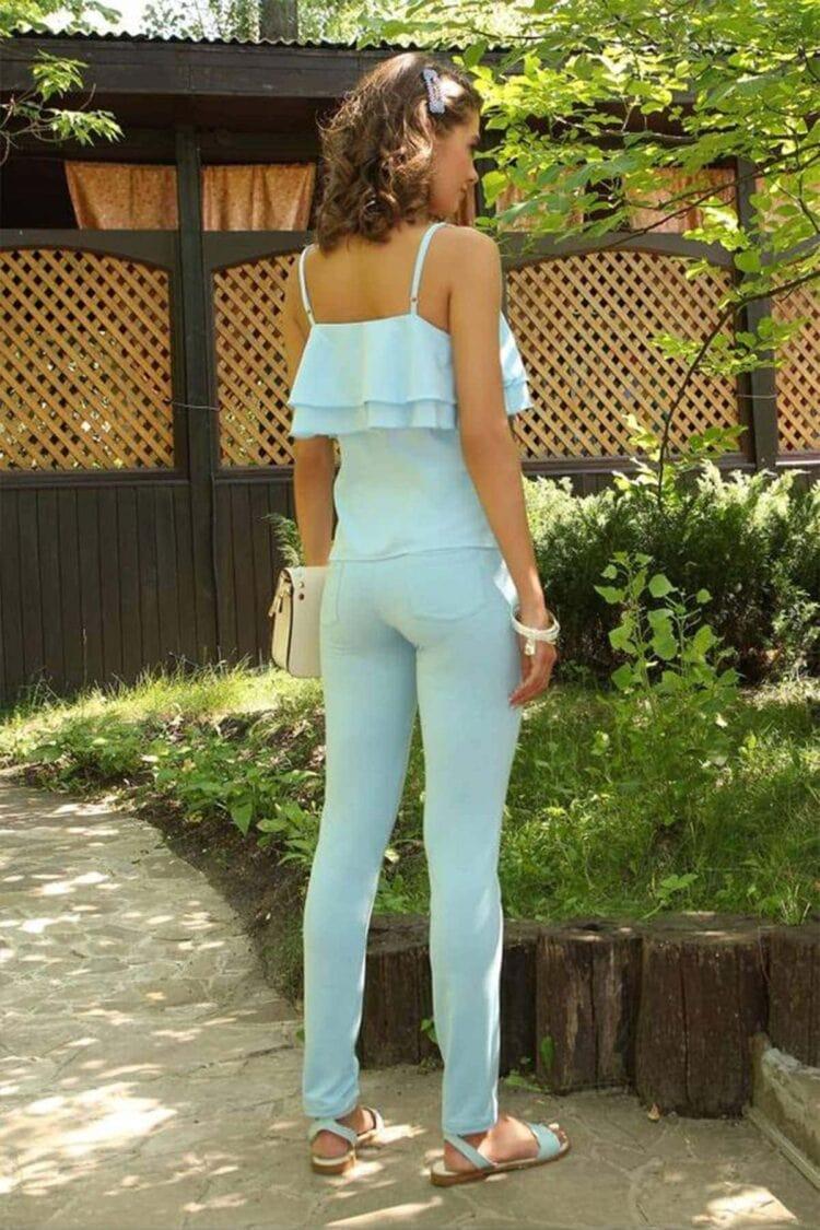Nusisukusi mergina apsirengusi šviesiai mėlyna spalva vasaros sezonu