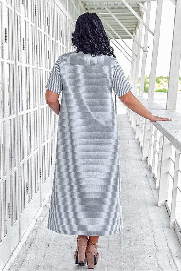 Moteris nusisukusi su didelio dydžio vasarine ilga lino dryžuota šviesia suknele trumpomis rankovėmis