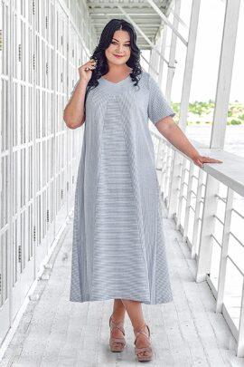 Moteris su didelio dydžio vasarine ilga lino dryžuota šviesia suknele trumpomis rankovėmis