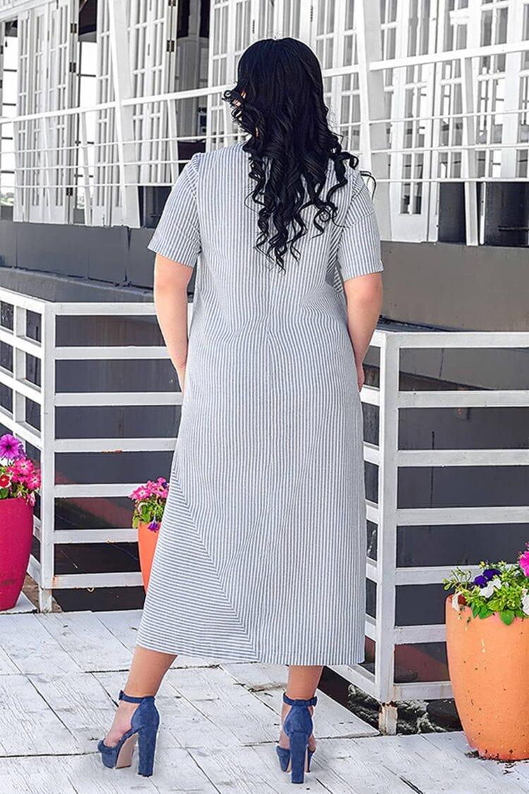Moteris su linine dryžuota šviesia suknele trumpomis rankovėmis