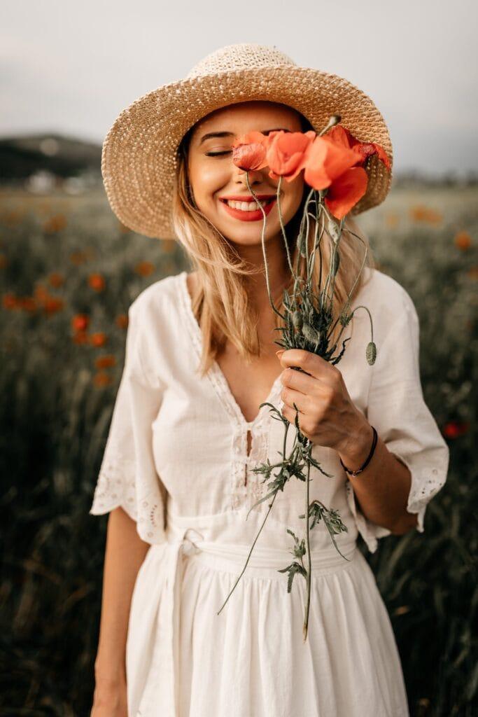 Boho stilius balta romantiška suknelė laiminga mergina su skrybėle ir raudonos aguonos