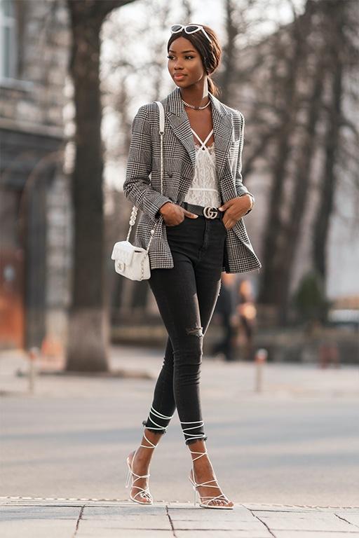 Elegantiškas drabužių derinys su juodais džinsais ir languotu švarku mieste